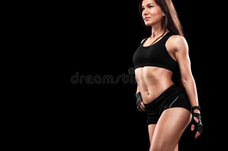 Stående av en passform och muskulös kvinna på svart bakgrund Crossfit genomköraremotivation royaltyfri fotografi