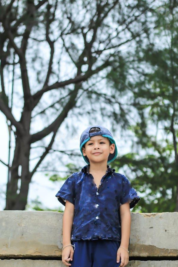 Stående av en pojke Asien bak träd royaltyfria foton