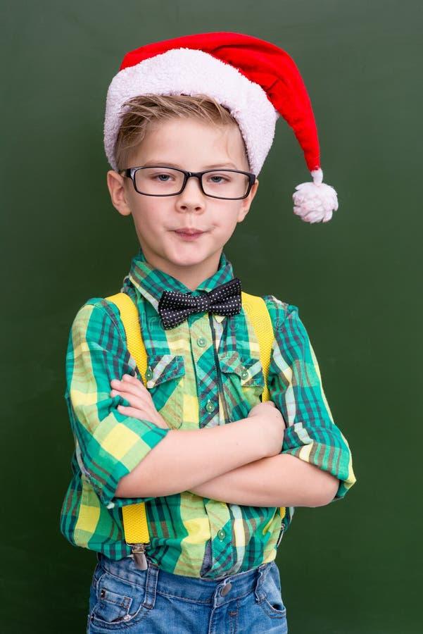 Stående av en pojke i jullocket nära en skolförvaltning arkivbild