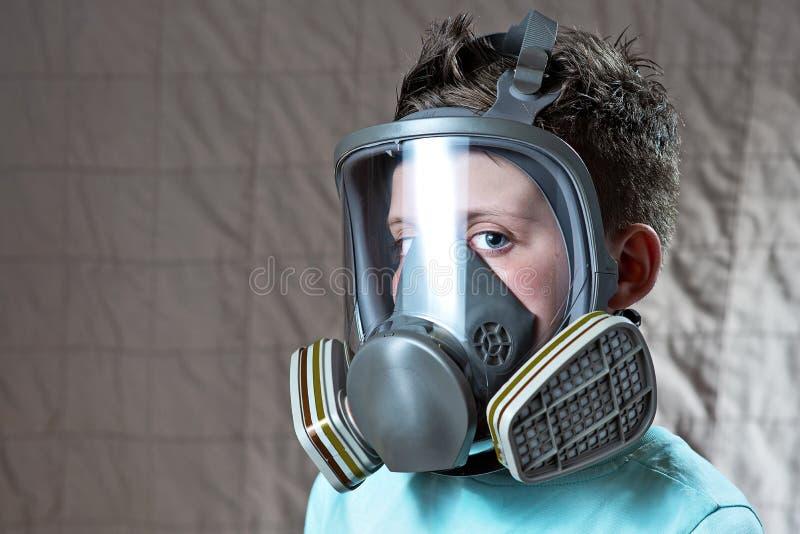 Stående av en pojke i en ljus t-skjorta med en gasmask arkivfoto