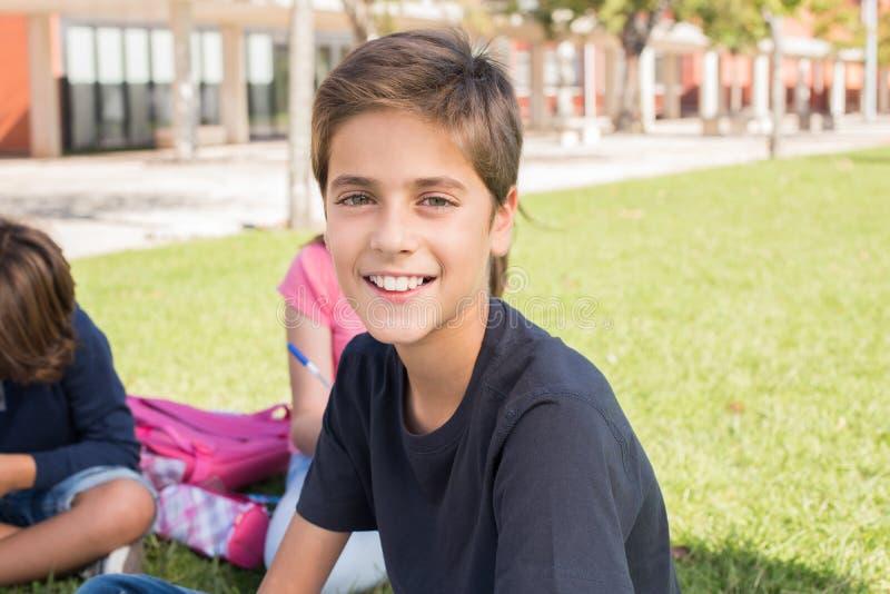 Stående av en pojke i skolauniversitetsområde arkivfoton
