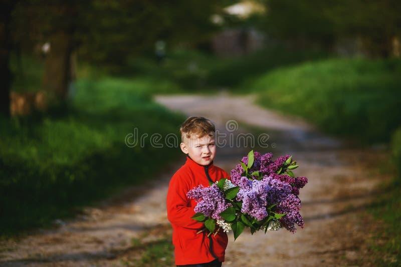Stående av en pojke med en bukett av lilor royaltyfri fotografi