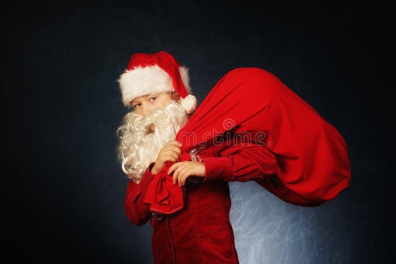 Stående av en pojke som kläs som Santa Claus glad jul arkivfoto