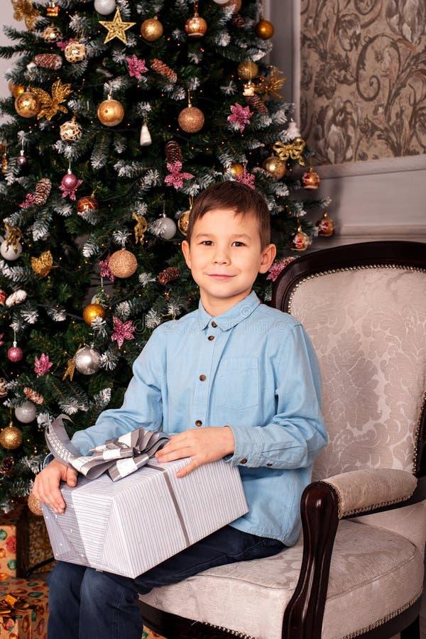 Stående av en pojke som sitter i en fåtölj nära ett träd för nytt år med en gåvaask i hans händer royaltyfria foton