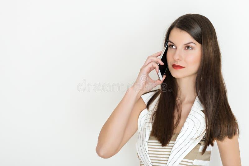 Stående av en positiv affärskvinna som talar på en telefon royaltyfri bild