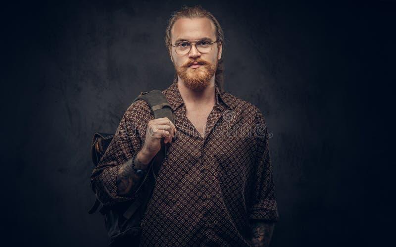 Stående av en rödhårig manhipsterstudent i iklädda exponeringsglas en brun skjorta, håll en ryggsäck som poserar på en studio arkivfoto