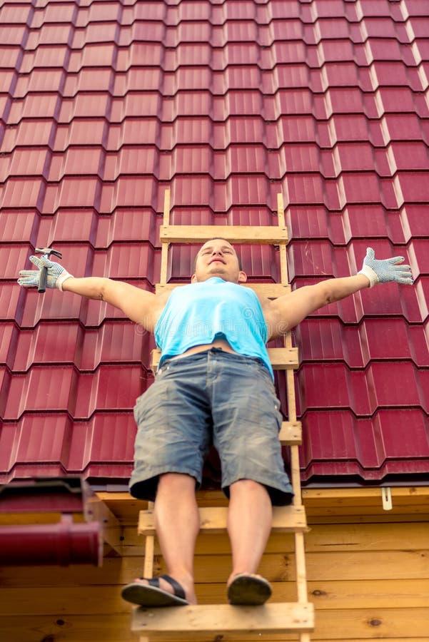 Stående av en repairman på en stege på taket, medan vila fotografering för bildbyråer