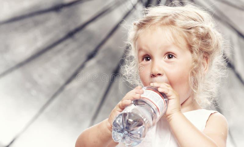 Stående av en rolig gullig liten flicka i en tillfällig klänning, drinkvatten, medan sitta i studio arkivbild