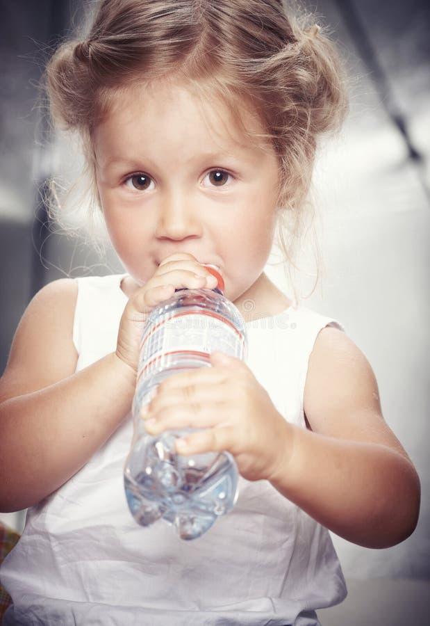 Stående av en rolig gullig liten flicka i en tillfällig klänning, drinkvatten, medan sitta i studio royaltyfri fotografi