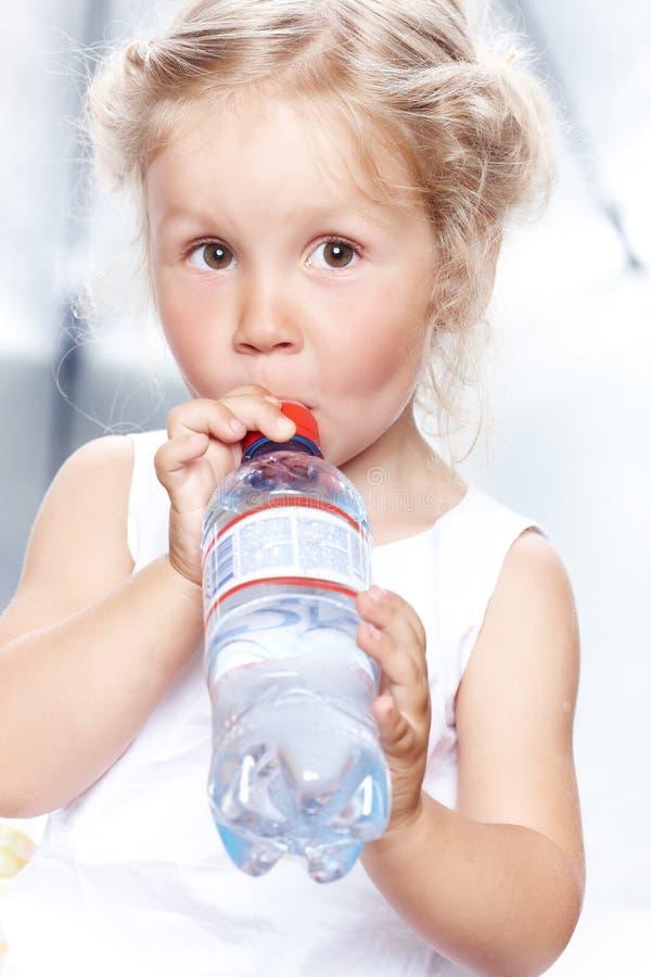 Stående av en rolig gullig liten flicka i en tillfällig klänning, drinkvatten, medan sitta i studio royaltyfri foto