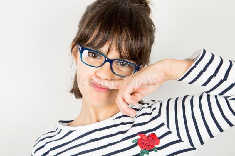 Stående av en rolig liten flicka med exponeringsglas som gör mustaschwi royaltyfri foto