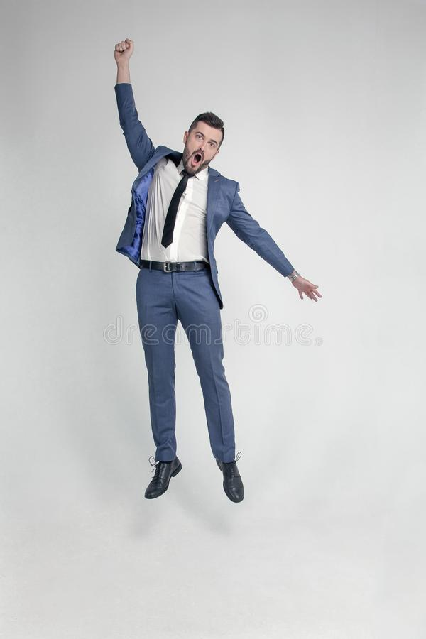 Stående av en rolig och liten galen affärsmanman som högt hoppar och hurrar på en vit bakgrund arkivbild