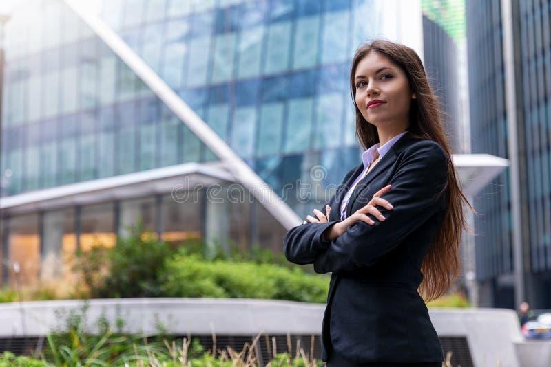 Stående av en säker affärskvinna framme av moderna kontorsbyggnader i staden royaltyfri foto