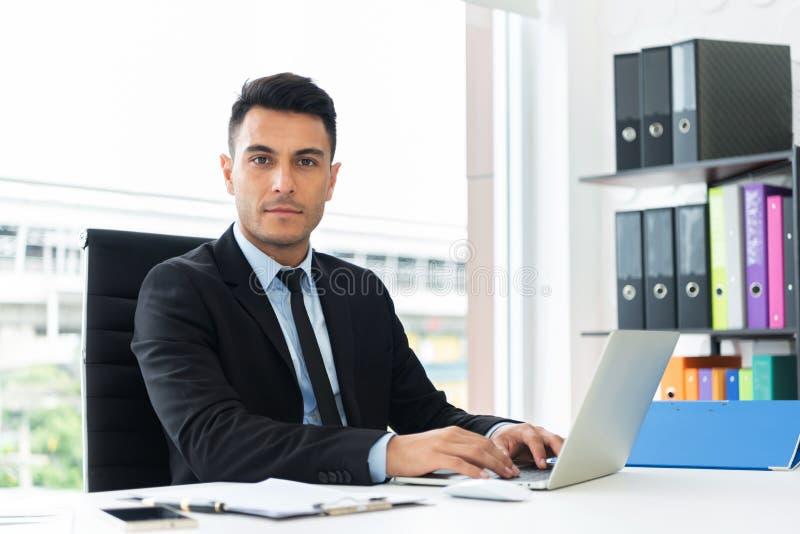 Stående av en säker affärsman som arbetar på bärbara datorn royaltyfria bilder