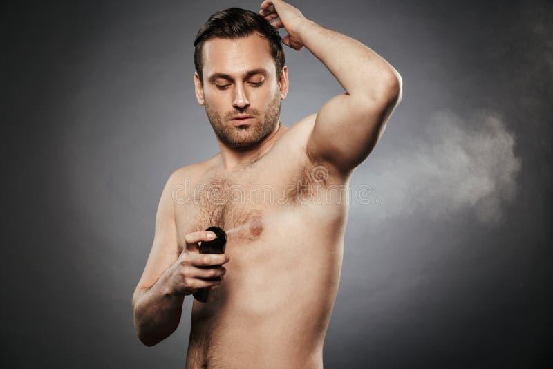Stående av en säker shirtless man som besprutar deodoranten arkivbild