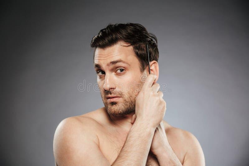 Stående av en säker shirtless man som kammar hans hår fotografering för bildbyråer