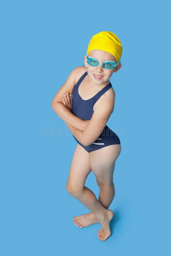 Stående av en säker ung flicka i swimwear över blå bakgrund arkivfoto
