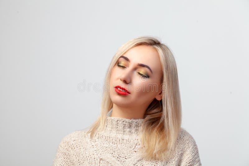 Stående av en sexig blondin med stängda ögon och makeup i den orientaliska stilen: ljus guld- brun skugga och röd läppstift på royaltyfria foton