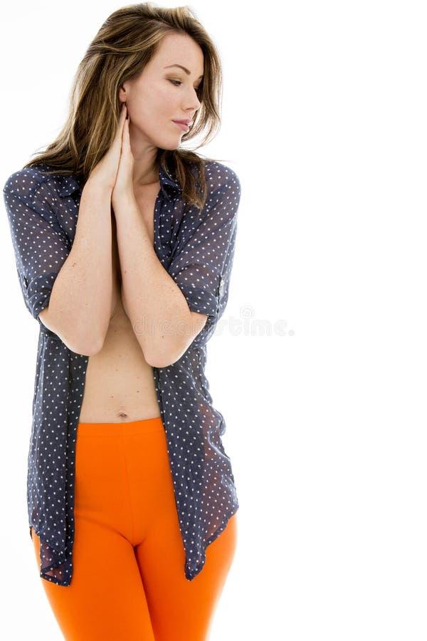 Stående av en sexig fundersam ung kvinna som bär en öppen skjorta arkivfoto
