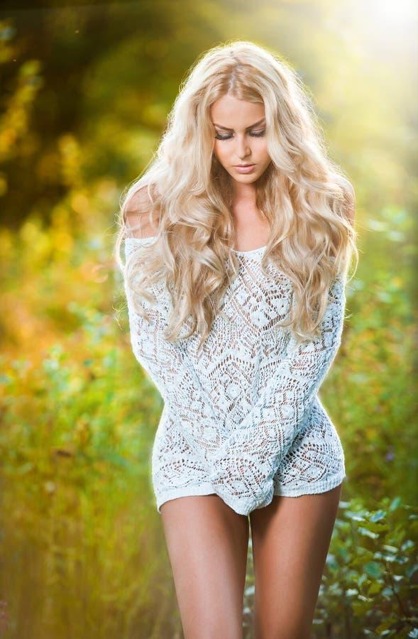 Stående av en sinnlig ung blond kvinnlig på fält i sexig vit kort klänning arkivbilder