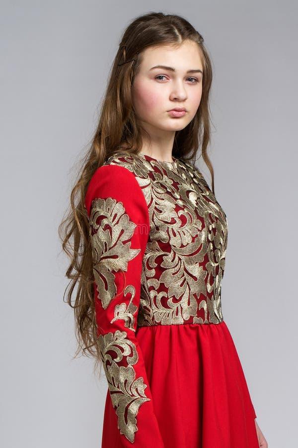 Stående av en sinnlig ung kvinna i röd klänning royaltyfri foto