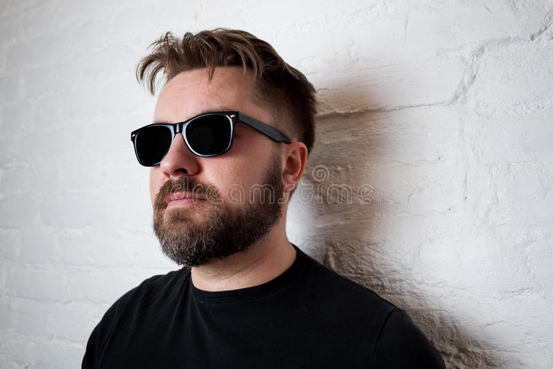 Stående av en skäggig allvarlig man i solglasögon och tillfällig kläder mot en vit tegelstenvägg royaltyfri fotografi