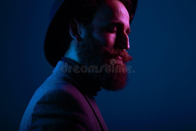 Stående av en skäggig man i hatt och dräkten, med nära ögon som poserar i profil i studion som isoleras på blå bakgrund arkivbild