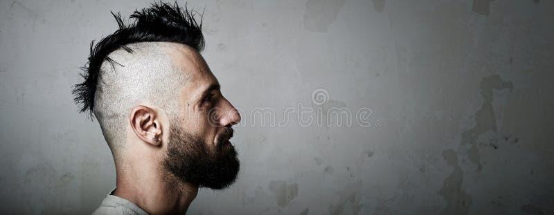 Stående av en skäggig man med mohawk konkret fotografering för bildbyråer