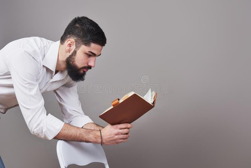 Stående av en skäggig ung man som bär en vitt skjorta och innehav en öppen stadsplanerare och en penna En grå väggbakgrund royaltyfri bild