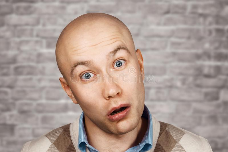Stående av en skallig dum förvånad grabb med den öppna munnen på en bakgrund för tegelstenvägg royaltyfria foton
