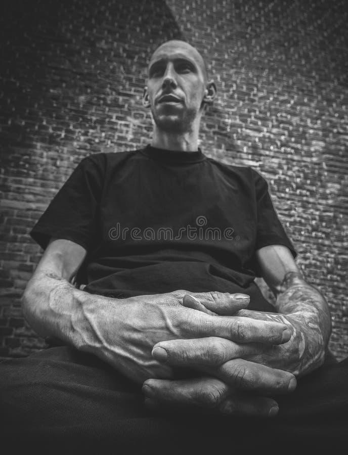 Stående av en skallig man med ett brutalt utseende och armar med tatueringar i förgrunden i svartvitt arkivbild