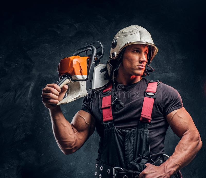 Stående av en skogsarbetare som bär skyddande kläder som poserar med en chainsaw arkivbild