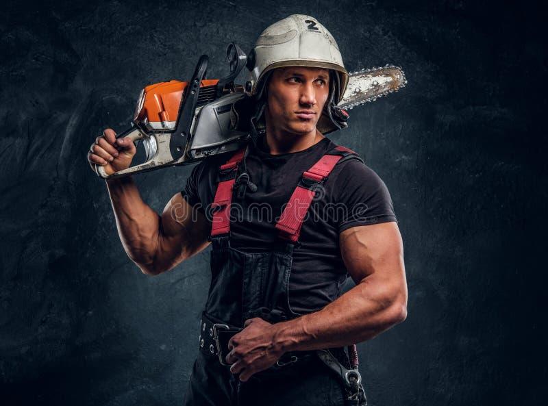Stående av en skogsarbetare som bär skyddande kläder som poserar med en chainsaw royaltyfri fotografi