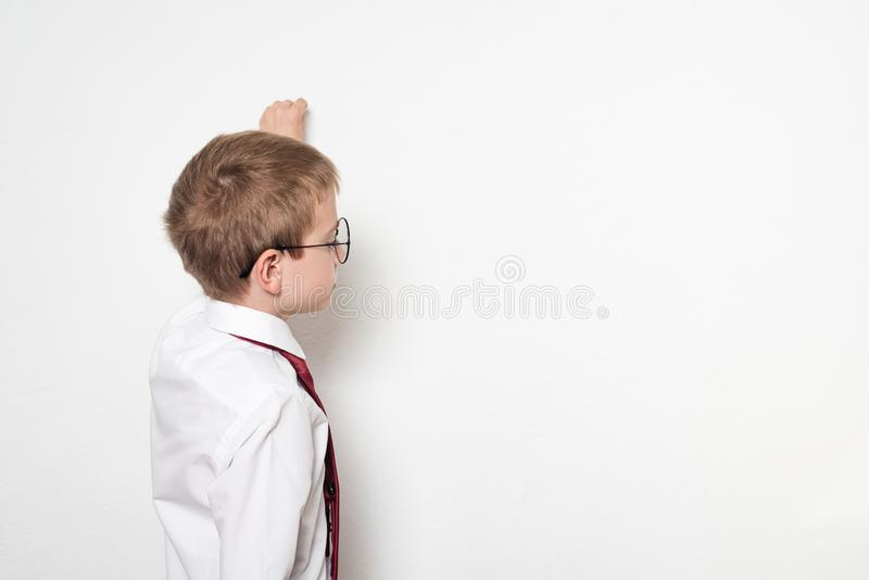 Stående av en skolpojke i runda exponeringsglas Låtsar för att skriva på den svart tavlan Vit bakgrund fotografering för bildbyråer