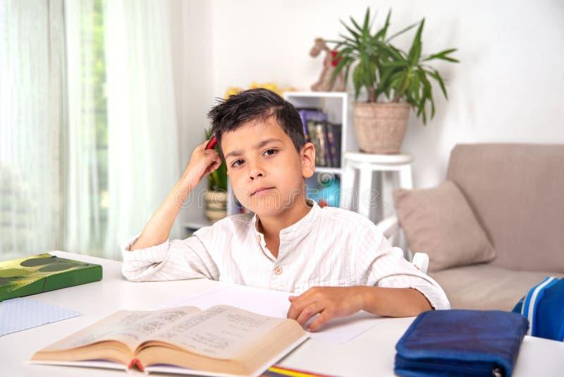 Stående av en skolpojke som sitter på tabellen och gör kurser arkivbilder