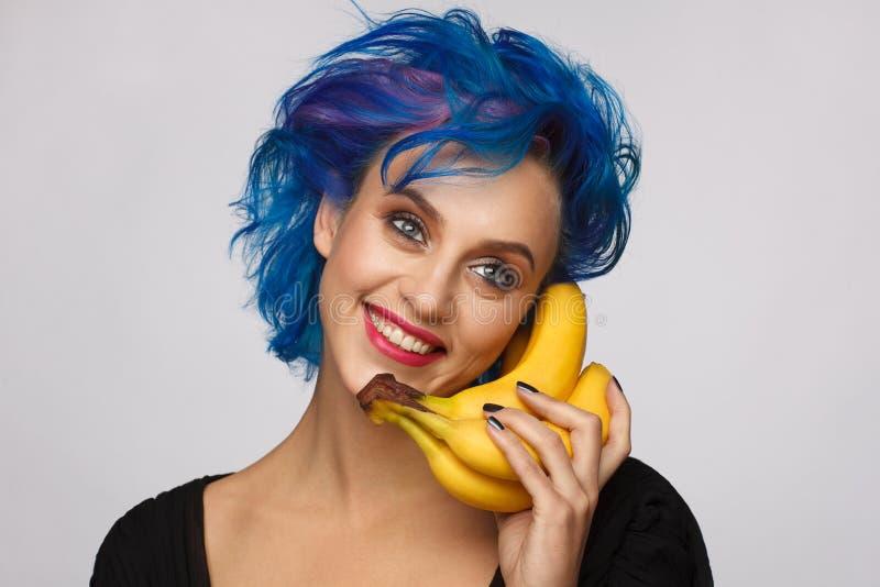 Stående av en skratta kvinna med blått och rosa hår som rymmer bananer i hennes hand som en telefon Lampa - grå bakgrund royaltyfria foton