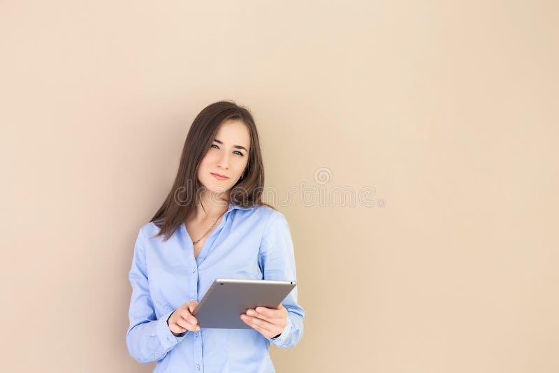 Stående av en smart säker flicka med en minnestavla i hand royaltyfri fotografi