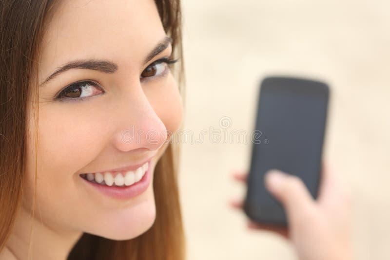 Stående av en smileykvinna som använder en smart telefon arkivbild