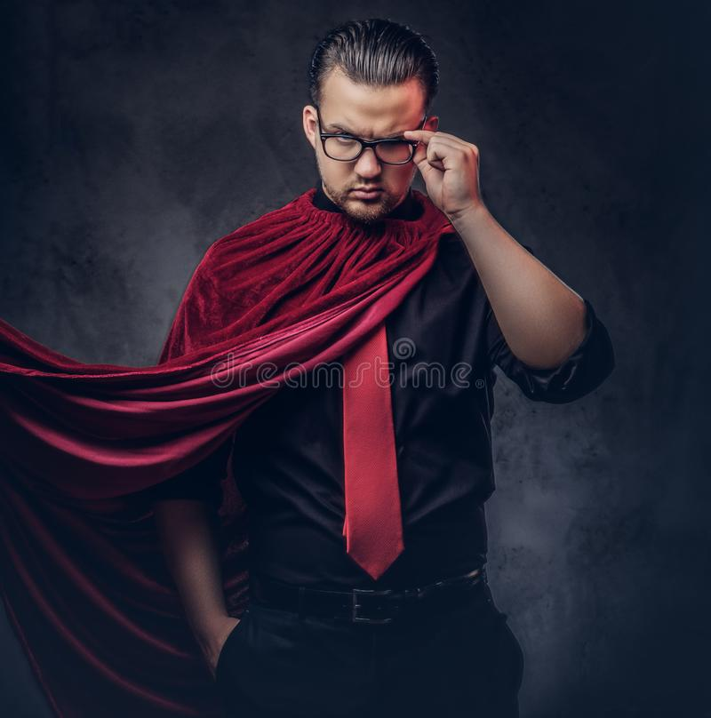 Stående av en snillerackaresuperhero i en svart skjorta med ett rött band royaltyfri foto