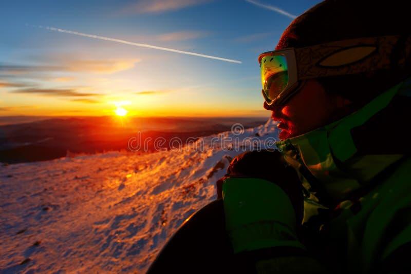 Stående av en snowboarder på en bakgrund av en solnedgång fotografering för bildbyråer