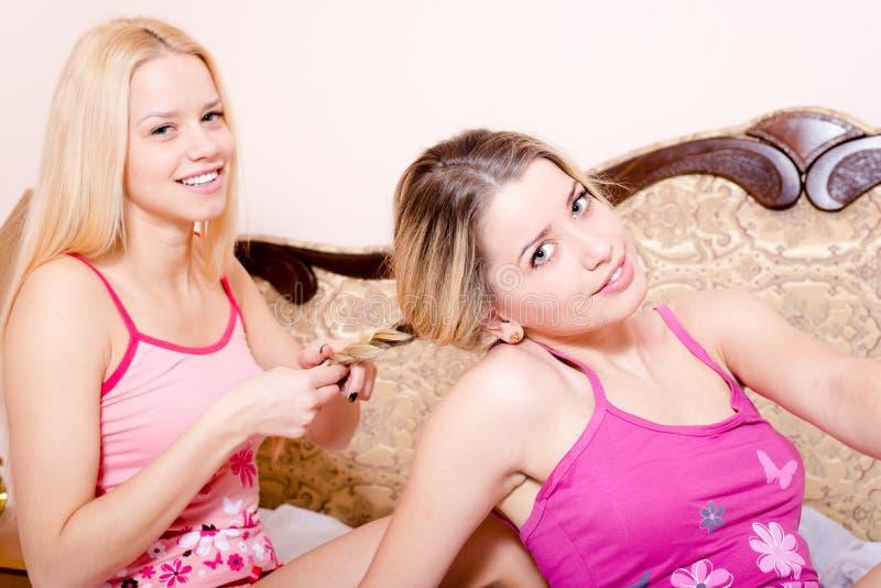 Stående av en som gör annan kvinnor för vänner för flätad trådråttsvansflicka som attraktiva unga blonda sitter i säng i pyjamas royaltyfri fotografi