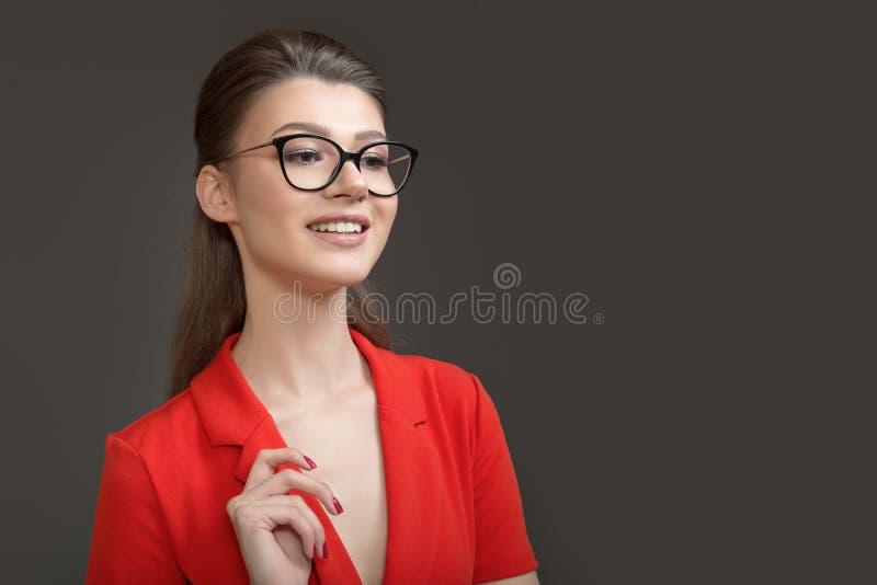 Stående av en stilfull affärskvinna med exponeringsglas n?tt leende Stranda av h?r v?nder mot in royaltyfria foton