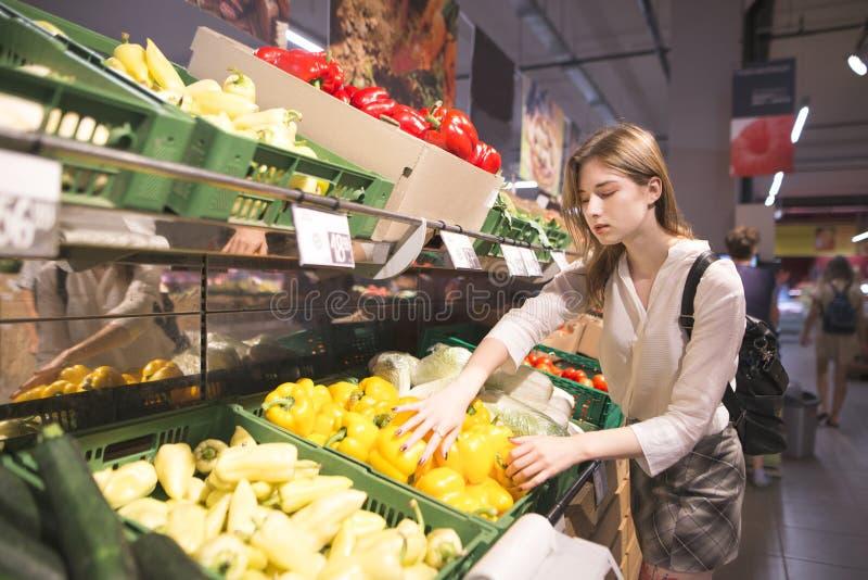 Stående av en stilfull flicka som köper peppar i grönsakavdelningen av supermarket arkivfoto