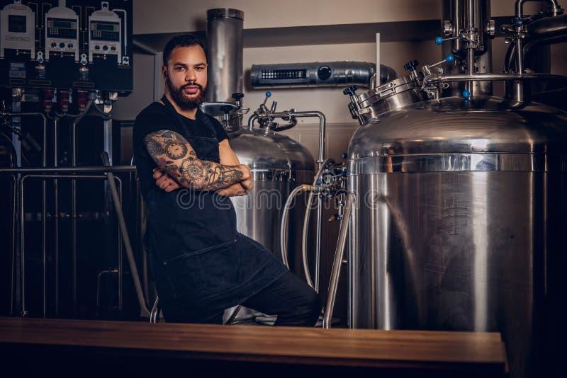 Stående av en stilfull skäggig tatuerad mörker flådd man med korsade armar som står bak räknaren i bryggeriet arkivbilder