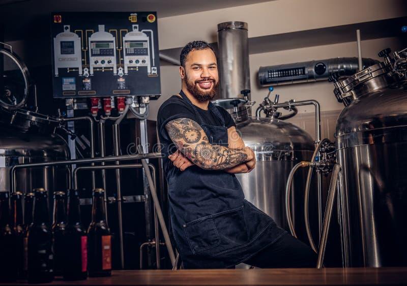 Stående av en stilfull skäggig tatuerad mörker flådd man med korsade armar som står bak räknaren i bryggeriet arkivbild