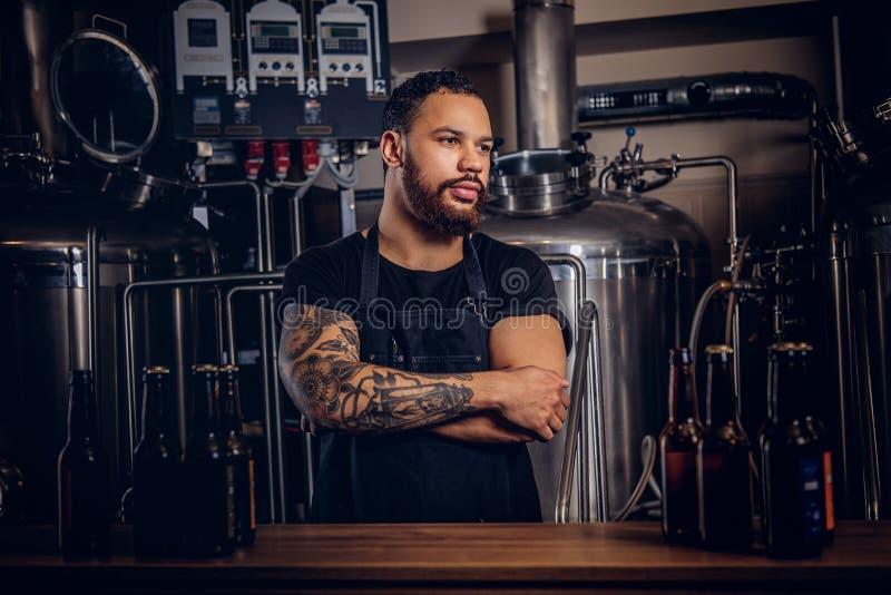Stående av en stilfull skäggig tatuerad mörker flådd man med korsade armar som står bak räknaren i ett bryggeri arkivbild