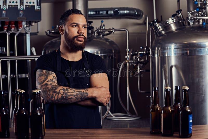 Stående av en stilfull skäggig tatuerad mörker flådd man med korsade armar som står bak räknaren i ett bryggeri arkivfoto
