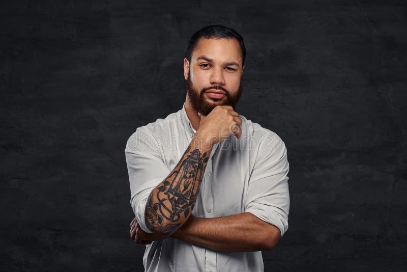 Stående av en stilig afrikansk amerikan tatuerad man med stilfullt hår och skägget i en vit skjorta som rymmer handen på hans arkivbilder
