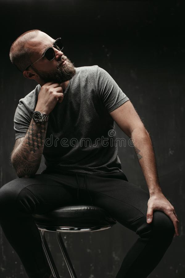 Stående av en stilig bliven skallig man med lång väl klippt bärande solglasögon för skägg och gråa skjortan som bort ser för att  arkivfoto