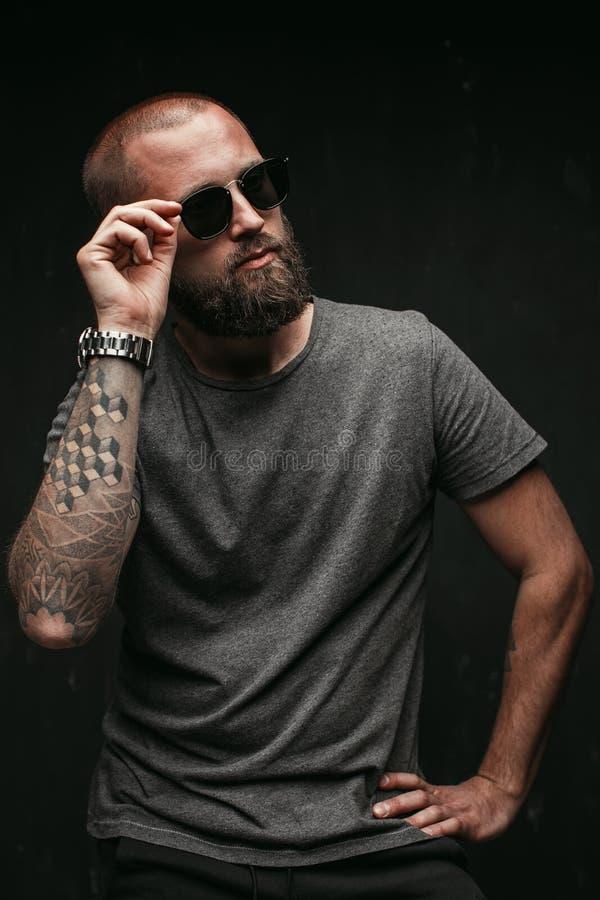 Stående av en stilig bliven skallig man med lång väl klippt bärande solglasögon för skägg och gråa skjortan som bort ser för att  royaltyfria foton